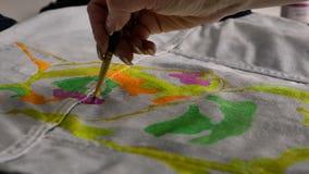 Una morenita aplica la pintura rosada con un cepillo a la tela Un ejemplo de bull terrier se representa en la chaqueta