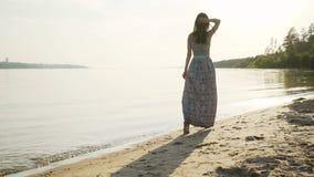 Una morenita con el pelo largo da un paseo a lo largo de la playa a lo largo de la playa en la puesta del sol almacen de metraje de vídeo