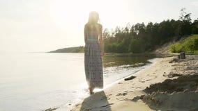 Una morenita con el pelo largo da un paseo a lo largo de la playa a lo largo de la playa en la puesta del sol almacen de video