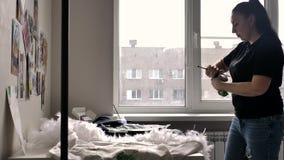 Una morenita en una camiseta negra y vaqueros dibuja en la chaqueta un ejemplo de bull terrier cerca de la ventana Hay mucho
