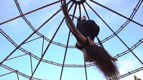 Una morenita flexible cuelga al revés en un anillo para la acrobacia aérea y los arcos metrajes
