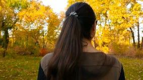 Una morenita hermosa con los vidrios camina a través de los árboles hermosos del bosque del otoño Cámara lenta Primer almacen de metraje de vídeo