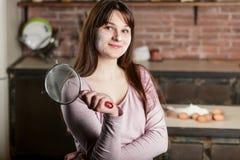 Una morenita joven tamiza a través de un tamiz en una tabla de cocina En los huevos de la endecha de la tabla fotografía de archivo libre de regalías