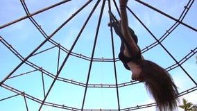 Una morenita linda cuelga al revés en el anillo en el aire y las vueltas, cámara lenta almacen de metraje de vídeo