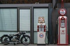 Una motocicleta vieja y dos bombas de gasolina retras imagen de archivo