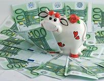 Una mucca la banca dei soldi sul pascolo dei soldi Fotografie Stock
