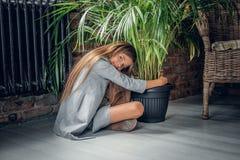 Una muchacha abraza el pote con la planta verde Fotografía de archivo libre de regalías