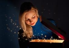 Una muchacha abre un rectángulo con un regalo Fotos de archivo