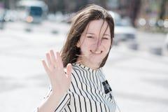 Una muchacha activa joven agita su mano para decir adiós foto de archivo libre de regalías
