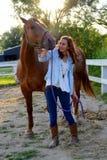 Una muchacha adolescente camina con su caballo Fotografía de archivo