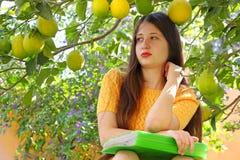 Una muchacha adolescente de la edad está aprendiendo en el jardín debajo de un árbol de limón Fotografía de archivo libre de regalías