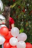 Una muchacha adolescente de la edad de la parte posterior con los globos rojos y blancos Foto de archivo libre de regalías