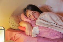 Una muchacha adolescente enferma de la edad miente en cama Fotografía de archivo libre de regalías