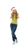 Una muchacha adolescente feliz que sostiene los pulgares para arriba en un sombrero de la Navidad Foto de archivo