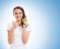 Una muchacha adolescente feliz que sostiene una manzana verde Fotografía de archivo