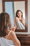 Una muchacha adolescente hermosa estudia su aspecto mientras que ella mira en el espejo Fotografía de archivo