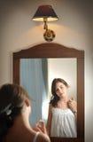 Una muchacha adolescente hermosa estudia su aspecto mientras que ella mira en el espejo Fotografía de archivo libre de regalías