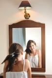 Una muchacha adolescente hermosa estudia su aspecto mientras que ella mira en el espejo Foto de archivo libre de regalías
