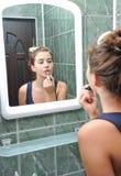 Una muchacha adolescente hermosa que pone el lápiz labial y que comprueba si ella mira muy bien Fotografía de archivo