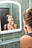 Una muchacha adolescente hermosa que pone el lápiz labial y que comprueba si ella mira muy bien Foto de archivo libre de regalías