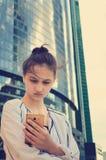 Una muchacha adolescente hermosa se coloca en un fondo de edificios modernos y sostiene un smartphone en sus manos fotografía de archivo libre de regalías