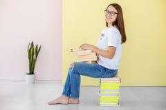 Una muchacha adolescente joven lleva a cabo muchos libros y risas Concepto de educación, de afición, de estudio y de mundo fotos de archivo