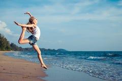 Una muchacha adolescente que salta en la playa en el tiempo del día Imagen de archivo libre de regalías
