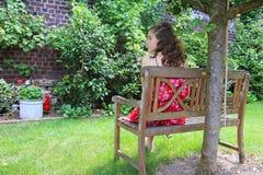 Una muchacha adolescente que se sienta en el jardín Foto de archivo libre de regalías