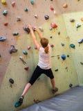 Una muchacha adolescente que sube en una pared de la escalada Imágenes de archivo libres de regalías