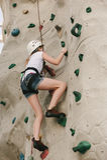 Una muchacha adolescente que sube en una pared de la roca. Imagen de archivo