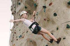 Una muchacha adolescente que sube en una pared de la roca que se inclina detrás contra el dispositivo de protección en caso de vol Fotografía de archivo