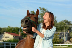 Una muchacha adolescente ríe con su caballo Imágenes de archivo libres de regalías