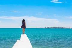 Una muchacha adolescente se coloca en el mar de la turquesa del fondo Fotografía de archivo libre de regalías