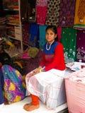 Una muchacha, adolescente - vendedor de telas en una tienda de la calle Fotos de archivo libres de regalías