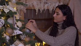 Una muchacha adorna un árbol de navidad con una bola hermosa que tiene un buen humor almacen de video