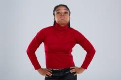 Una muchacha afroamericana divertida que pone mala cara sus labios y que se sostiene los brazos al lado Fotografía de archivo