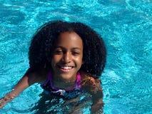 Una muchacha afroamericana hermosa en la piscina Fotos de archivo