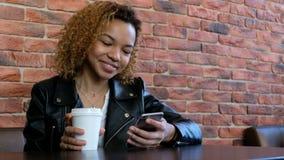 Una muchacha afroamericana hermosa moderna joven es el hablar sonriente en el teléfono y consumición de una bebida de una taza bl almacen de video