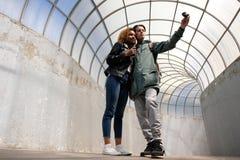 Una muchacha afroamericana joven y un individuo europeo hacen un salfi con una pequeña cámara de la acción Gente dentro de los wi imágenes de archivo libres de regalías