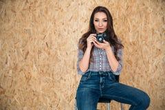Una muchacha agradable con un look sexy se está sentando en una silla en su estudio, y está consiguiendo lista para tomar una fot imagen de archivo libre de regalías