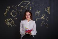 Una muchacha agradable, escribe en los cuadernos, colocándose cerca de un tablero con la imagen de muestras de ideas, de la cienc fotografía de archivo libre de regalías