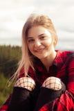 Una muchacha agradable se está sentando al aire libre Foto de archivo