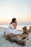 Una muchacha agradable se sienta en la orilla de mar por la tarde imagen de archivo