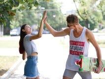 Una muchacha alegre que da a cinco su novio lindo con un longboard en un fondo borroso del parque Relación y amor Fotos de archivo libres de regalías