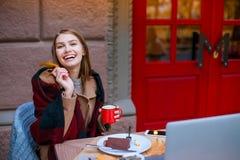 Una muchacha alegre, sentándose en un café, sosteniendo una taza y una hoja amarilla del otoño, y sonriendo feliz Fotografía de archivo