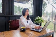Una muchacha asiática en la camisa blanca juega el cuaderno en la tabla de madera en sitio negro Foto de archivo