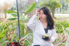 Una muchacha asiática en la capa blanca que sienta y que sostiene una taza de café negra en su mano en el banco blanco bajo luz d Fotografía de archivo