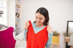 Una muchacha asiática preciosa que intenta en el nuevo vestido en casa Fotos de archivo libres de regalías