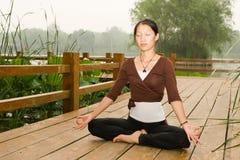 Una muchacha asiática que hace yoga Foto de archivo libre de regalías