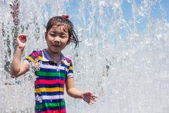 Una muchacha asiática que juega por la fuente de agua Imagen de archivo libre de regalías